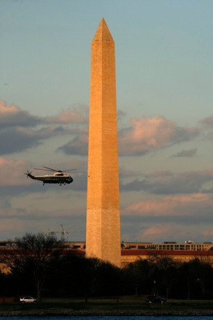 Presidential helicopter Marine One flies by Washington Monument at sunset.